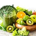Een schaal vol met fruit zoals kiwi, appel, sinnaasappel en glas met groen sap