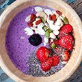 Hout schaaltje met paarse vloeistof versierd met aardbeien, blauwe bessen en pijnboompitten