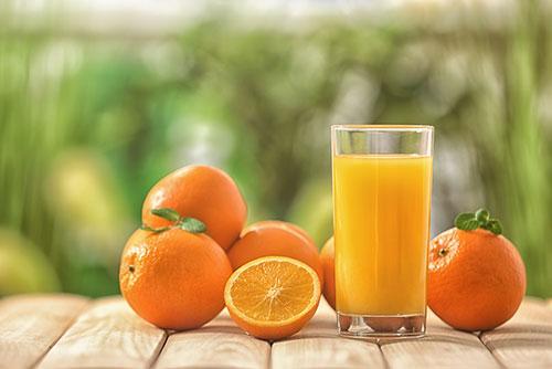 Tafel met daarop meerdere sinaasappels en een glas sinaasappelsap