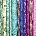 Stapel van opgevouwen lappen stof in de kleuren groen, lichtblauw, paars en roze