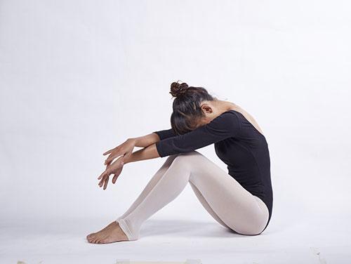 Vrouw in een turn pakje met witte legging die op de grond zit met haar gezicht tussen haar knieen