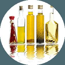 Vijf flessen met daarin verschillende soorten olie - zonnebloemolie en peperolie bijvoorbeeld
