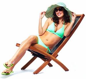 Vrouw in groene bikini met grote hoed die zit in een strandstoel