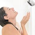 Een vrouw onder de douche, met haar gezicht richting de douchekop en haar handen in een kommetje
