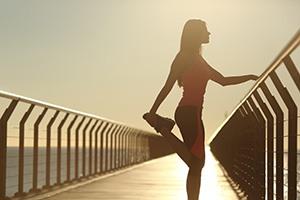 Vrouw die alleen op een brug staat en een sportoefening doet waarbij ze een van haar voeten via achter vast heeft