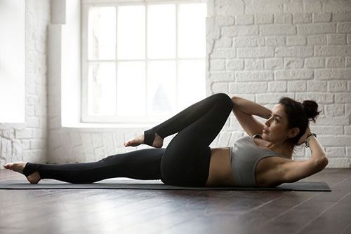 Vrouw in sportlegging en -top die op een matje ligt en een oefening doet