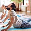 Een man met een donkere baard bij een yoga-les die op zijn buik ligt en zijn bovenlichaam naar boven duwt