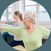 Een oudere mevrouw en jonge vrouw die bezig zijn met een yoga-oefening met hun arm gestrekt naar voor