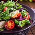 Een zwart bord met een salade met sla, tomaat, komkommer